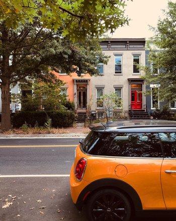 @feisty_foreigner - oranges Auto mit Reihenhäusern im Hintergrund