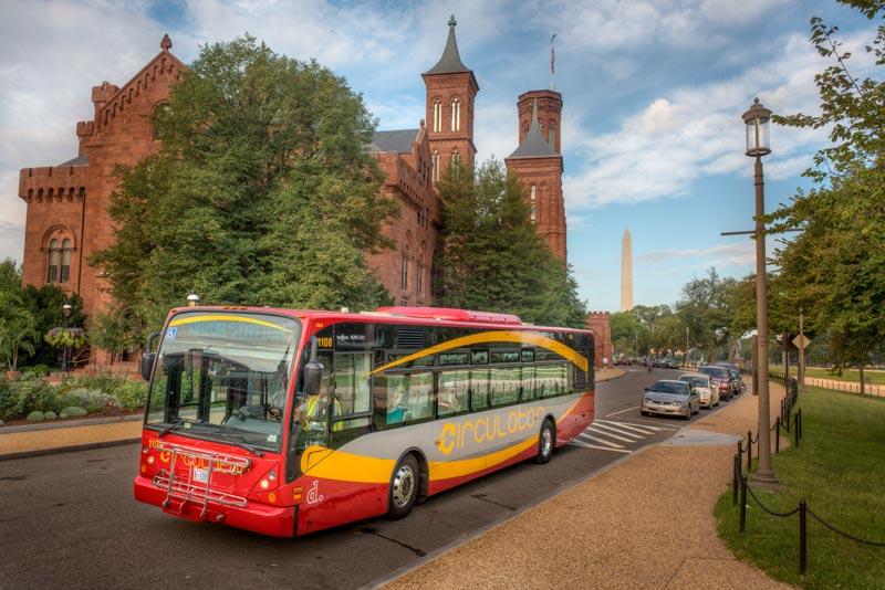 DC Circulator Bus in der National Mall vor dem Smithsonian Castle - Wie man sich in Washington, DC fortbewegt