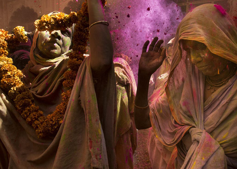 Women participate in the Holi ceremony, the festival of love and colors, which was once considered inappropriate for widows, at the Gopinath Temple in India.