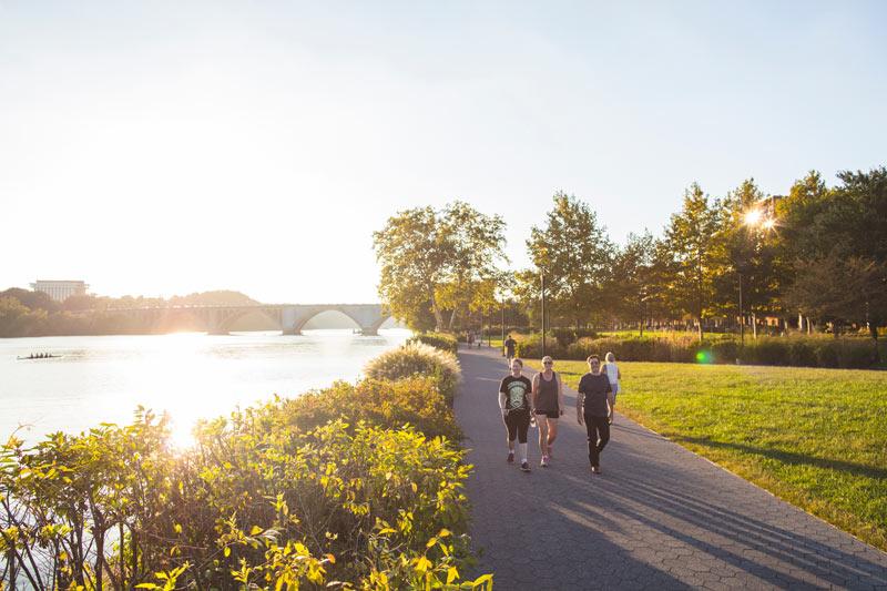 Gente caminando por Georgetown Waterfront Park en una tarde soleada en Washington, DC
