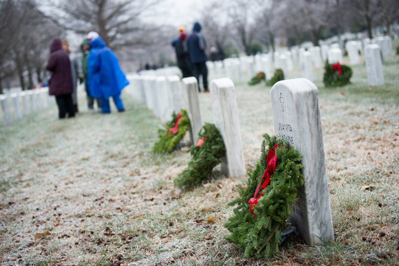 People lay wreaths at Arlington National Cemetery - National Wreaths Across America Day