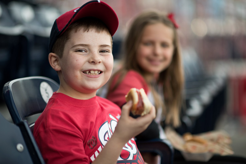 Young Nationals fan with hot dog - Where to eat and drink at Nationals Park in Washington, DC