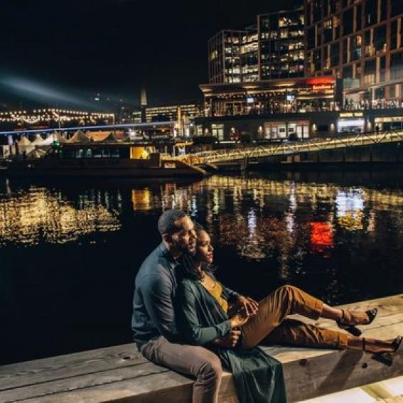 couple sitting by the wharf pier at night