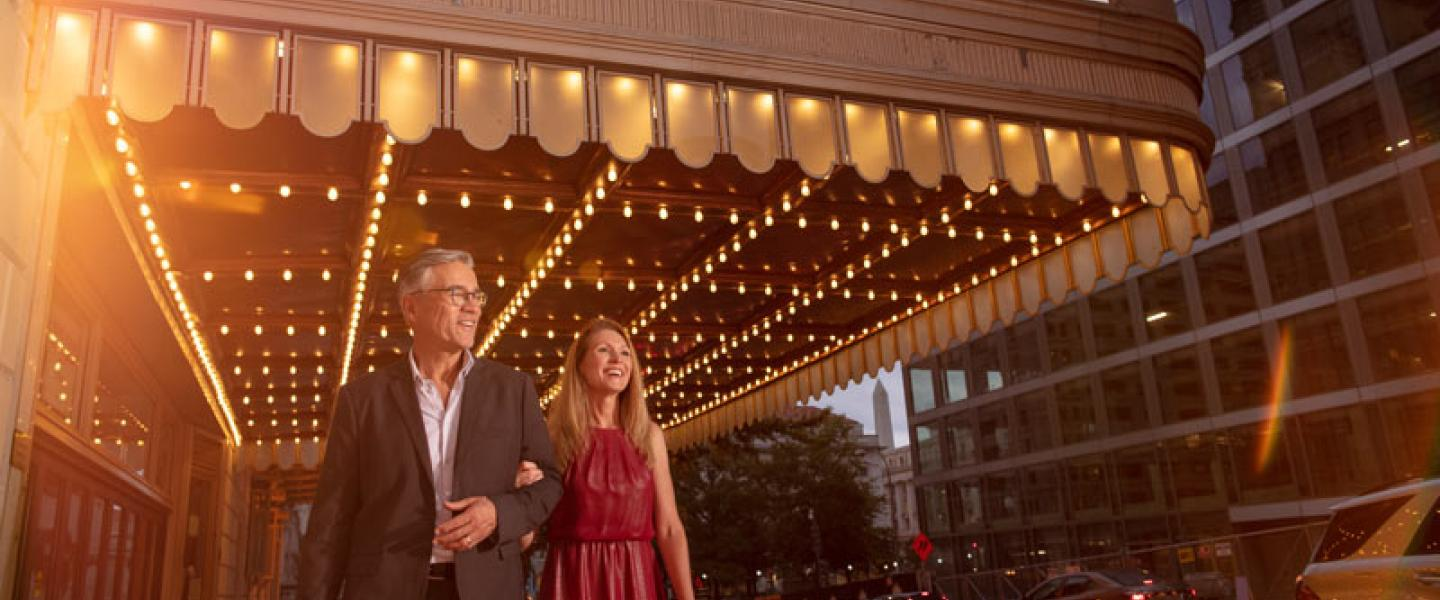 Theater and Performing Arts in Washington, DC - Couple walking under the Warner Theatre marquee in downtown DC